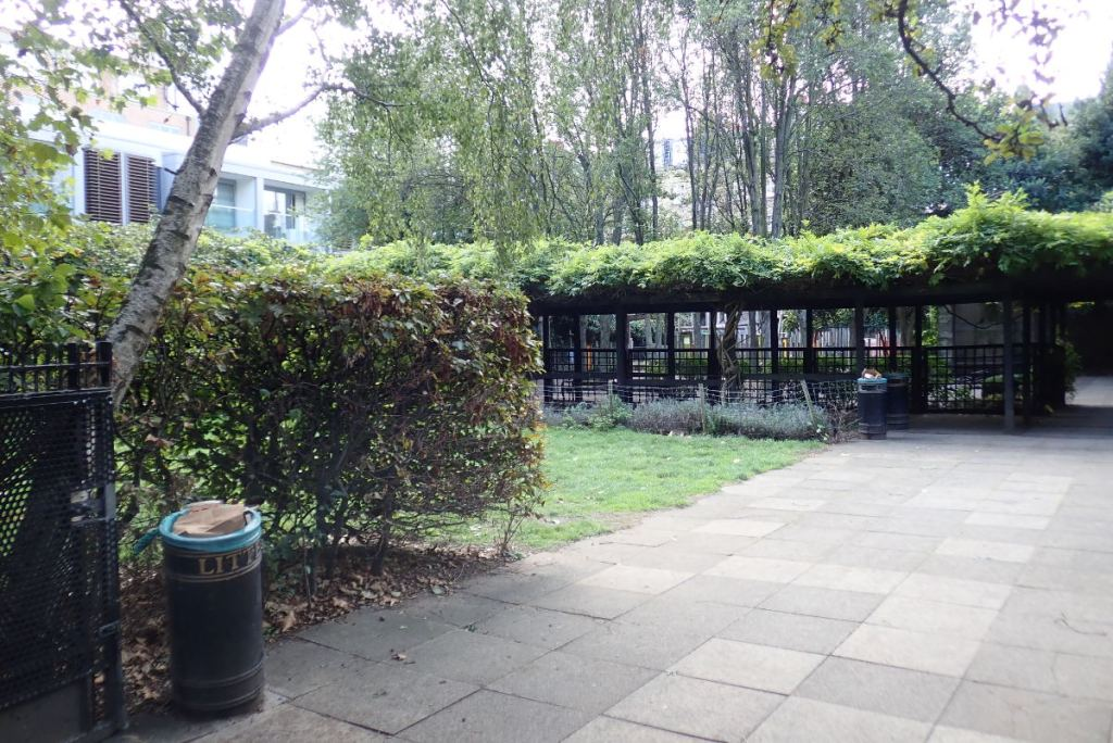 View of paved area and lawn in park.